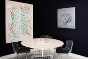 A tulip table and metal Bertoia chairs surrounded by black walls