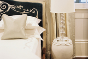 An upholstered bed beside a white garden stool topped with a crystal lamp