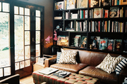 A leather couch and a tufted ottoman in a room with black built-in shelving
