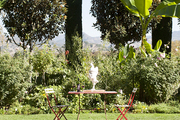 A red bistro table surrounded by verdant gardens