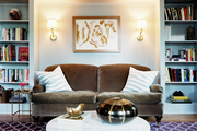 Built-in bookcases surrounding a brown couch and a pair of wall sconces