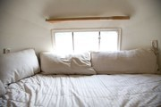 White linens in the cozy bedroom area of a vintage Airstream