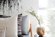 A detail of a contemporary bedroom with white walls and a black splatter paint mural.