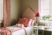 A guest bedroom with coordinating block-printed upholstery and window treatments