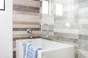 Contemporary bathroom with white tub and brown tiled wall.