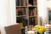 Contemporary hurricane lanterns and a vase of yellow roses atop a dining table