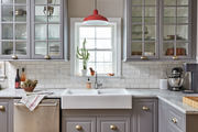 A red pendant light really pops in this gray and white kitchen.
