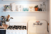 A skirted sink and open shelves with glassware and dishes