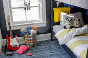 A boy's bedroom with a bunk bed, blue rug, chalkboard walls, and toys