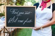 A chalkboard directs guests to a Bastille Day dinner party