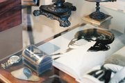 A glass tabletop layered above a wooden desk decorated with artful objects