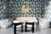 White midcentury furniture in a nook with geometric walls and a round mirror
