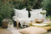 A neutral patio setting with a gold egg-shaped coffee table.
