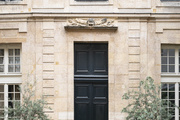 A stone exterior with large, black doors.