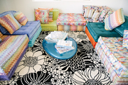 A multi patterned room filled with floral carpet and colorful seating areas.