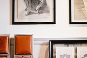A pair of leather chairs beside a grouping of framed art