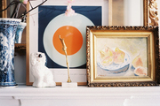 Framed art and a vase of flowering branches on a white mantel