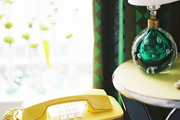 A green glass lamp beside a vintage yellow phone