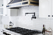 A dramatic black-and-gold range and hood with a pot filler in a contemporary white kitchen
