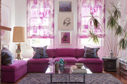 A pink couch and a glass-topped coffee table in a vibrant living room