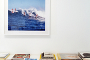 Framed artwork hung above a surface covered in books and catalogs