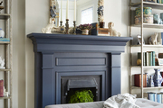 Coral framed mirror atop blue fireplace.