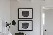 Framed Art hanging in white bedroom.