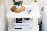 A white end table styled with books and flowers
