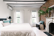 A neutral bedroom with a brick wall.