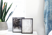 A bedside table with black and white photos.