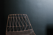 Wire chair against a black and white wall