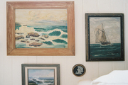 Ocean-themed paintings hung on white paneled walls