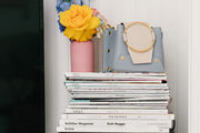 A large stack of magazines with a floral arrangement and purse sitting on top.