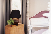 A wicker bedside table beside a four-poster bed