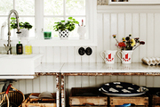 Wooden crates and a farmhouse sink in a kitchen with wainscoting