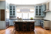 A traditional kitchen with blue cabinets and white tile walls.