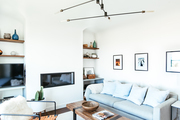 A contemporary living room with white walls and a gray sofa.