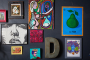 A gallery wall of colorful paintings.