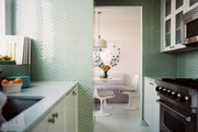 Green tile and white cabinets in a kitchen