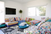 A multi patterned living room filled with floral carpet and colorful seating areas.
