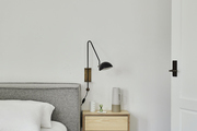 A detail of a gray bed frame and floating nightstand.