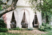 An outdoor living space with white curtains