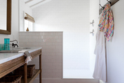 White subway tile and a striped rug in a bathroom