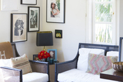 A wicker couch and armchair paired with an ottoman in a bedroom corner a bedroom