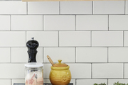 A close-up of a kitchen's wooden shelf, wall tile, and cooking essentials.
