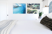 A white bedroom with vivid nature photographs.