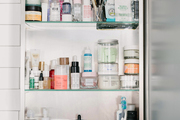 A bathroom storage cabinet with many beauty essentials.