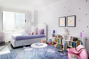 Playful girl's room with purple bedding and fun area to play with a view of the city.