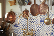 Mix and match tiled splashboard behind gold sink.