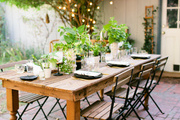 A rustic dining table and chairs with accents of greenery.